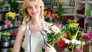 Female florist holding bunch of flowers in flower shop