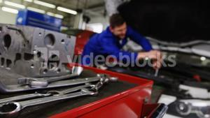 Car parts with tools and mechanic working in background