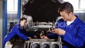 Male mechanic checking a car parts while female mechanic servicing a car