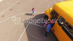Teacher giving high to kids while entering in bus