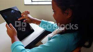 Schoolgirl using digital tablet in classroom at school
