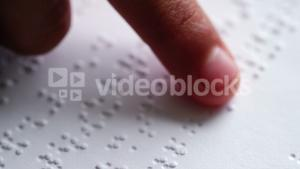 School kid reading a braille book in classroom at school