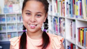 Portrait of schoolgirl holding stack of book in library at school