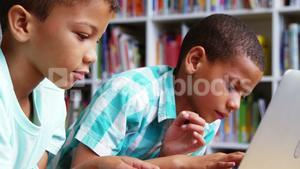 Schoolkids using laptop in library at school