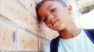 Schoolkid leaning on wall in corridor at school