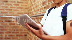 Schoolboy using digital tablet in school