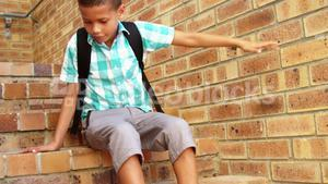 Sad schoolboy sitting alone on staircase at school