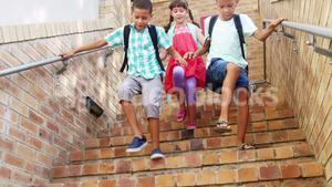 Smiling schoolkids walking on staircase at school