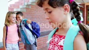 Schoolkid bullying a sad girl in corridor at school