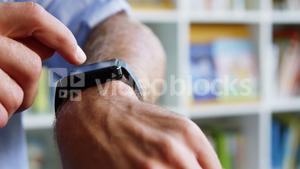 Close-up of teacher adjusting a smart watch in library at school