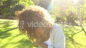 Woman blowing nose in park
