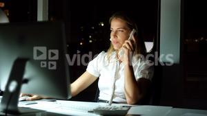 Businesswoman working over computer while talking on the phone