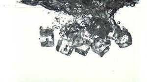 Ice cubes falling into water in super slow motion