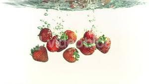 Strawberries falling into water in super slow motion