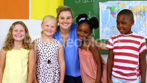 Portrait of teacher and kids smiling in classroom