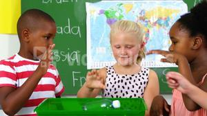 School kids putting waste bottle on recycle logo box in classroom