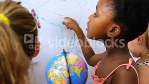 Kids studying globe in classroom