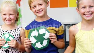 School kids holding recycling symbols and globe in classroom