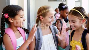 School kids giving high five to each other