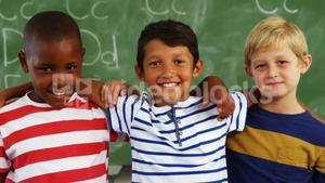 School kids standing together with arm around in classroom