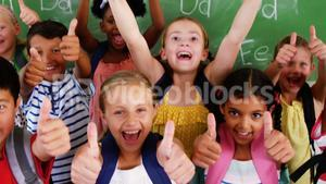 School kids showing thumbs up in classroom