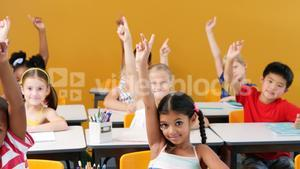 School kids raising hands in classroom