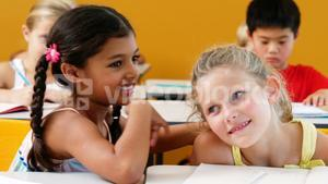 Schoolgirl whispering into her friend s ear in classroom
