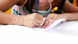 Schoolgirl writing on chit in classroom