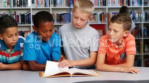 School kids reading book together in library