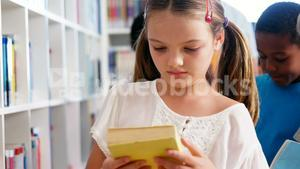 Girl looking at book in library