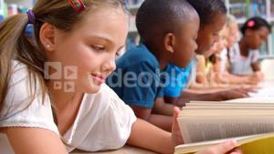 School kids reading book in library