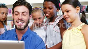 Teacher interacting with students while using digital tablet