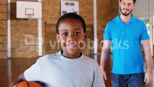 Sports teacher standing with his student in basketball court