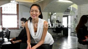 Smiling female hairstylist leaning on chair