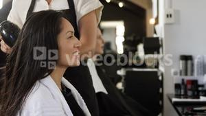 Woman getting her hair dried with hair dryer