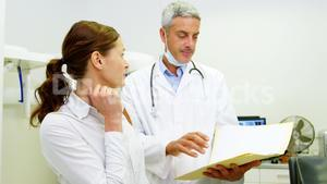 Dentist discussing report with female patient