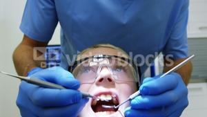 Dentist examining a young patient with tool