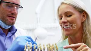 Dentist showing teeth shades to female patient