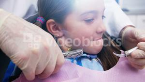 Dentist examining a young patient with tools