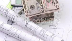 Dollar house, blueprints and calculator turning