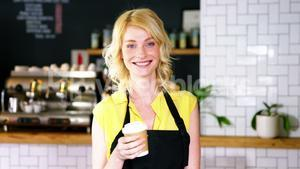 Portrait of waitress holding disposable coffee cup