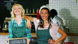 Portrait of waitress and coworker standing with merry x mas board