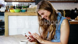 Woman using mobile phone in cafeteria