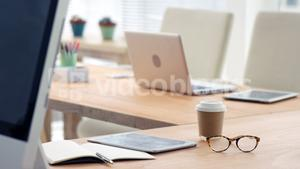 Spectacle, disposable coffee cup, laptop, computer and digital tablet on desk