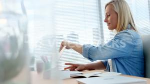 Businesswoman opening laptop at her desk