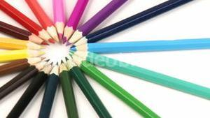Close up of colour pencils in a circle turning against white