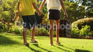 Boy and girl walking together with bag and soft toy