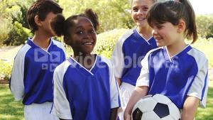 Group of smiling kids standing with football
