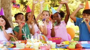 Group of kids blowing party horn while celebrating a birthday