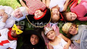 Group of kids in various costumes lying on grass